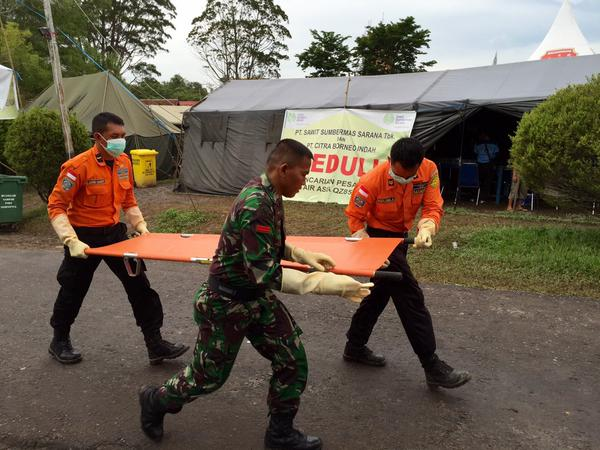 Personnel preparing to take another victim's body to hospital as it touches down now in Pangkalan Bun