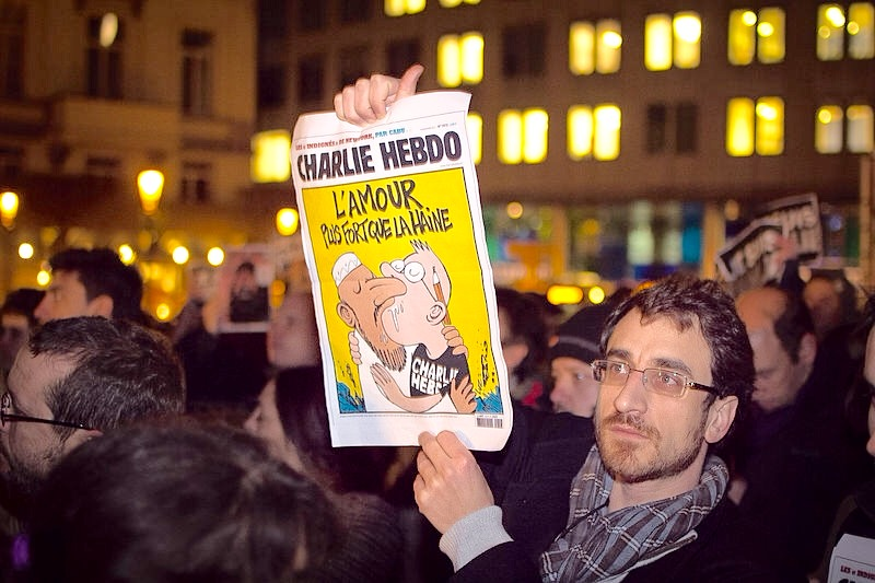 A supporter in Bologna, Italy, holds up a cartoon drawn by artists from the Charlie Hebdo Magazine. Know for its satirical material, the magazine has been a love or hate sensation in Europe's long lasting tradition of free speech