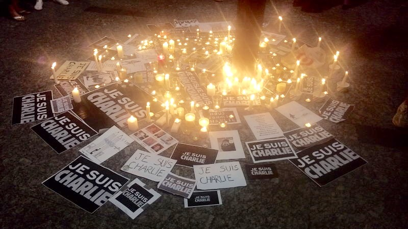 "Phrases of ""Je suis Charlie"" decorate an ornamental vigil in Brisbane, Australia, on the night following the first shootings. Candles were lit as a sign of peace and goodwill"