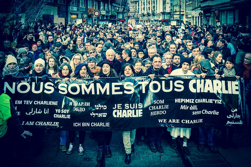 "A rally participates in the Republican Marches in Strasbourg, Northeastern France, with the front holding a banner reading ""Nous sommes tous Charlie"", meaning ""We are all Charlie""; the mood remains positive and bright"