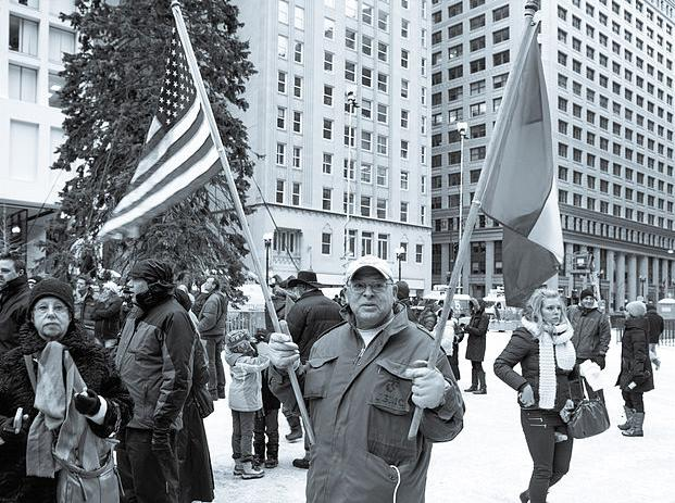 A man holding both a French and American flag at a rally in Daley Plaza, Chicago. France has seen ardent support even across the chilling Atlantic