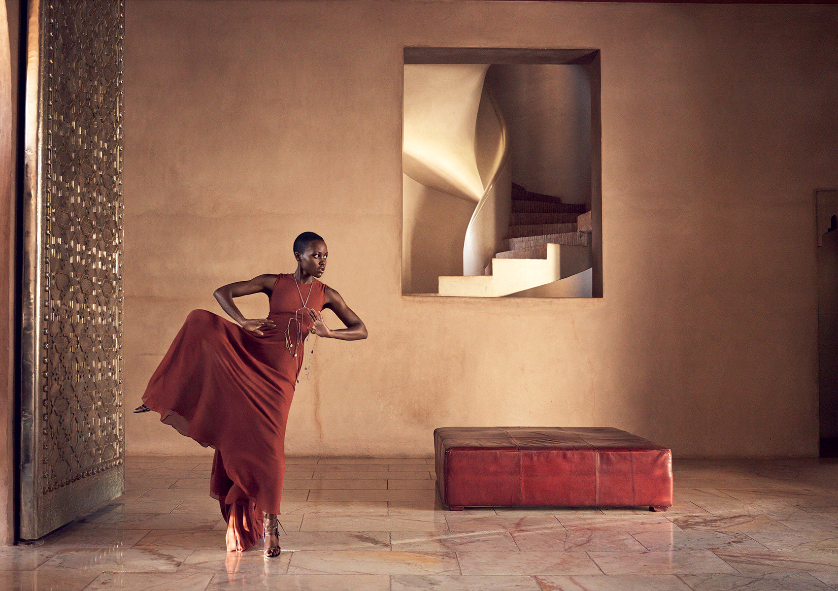 Nyong'o in the entrance hall of Marrakech's exclusive Ksar Char-Bagh resort, a chic retreat tucked away in the city's palm grove. Vera Wang Collection copper trapeze dress. Ann Demeulemeester necklace. Pebble London ring. Casadei for Prabal Gurung heels, worn throughout.