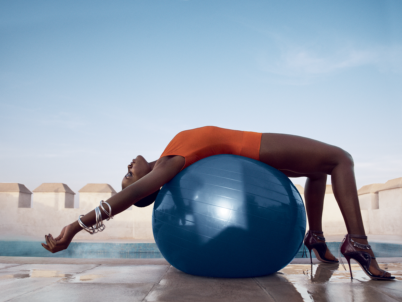 BODY AND SOUL: Nyong'o at a private dipping pool atop one of Ksar Char-Bagh's towers, which also boasts breathtaking views of the Atlas Mountains. Givenchy by Riccardo Tisci marigold bodysuit. Spinelli Kilcollin linked bangles. Georg Jensen double bangle. | CREDIT: Vogue.com