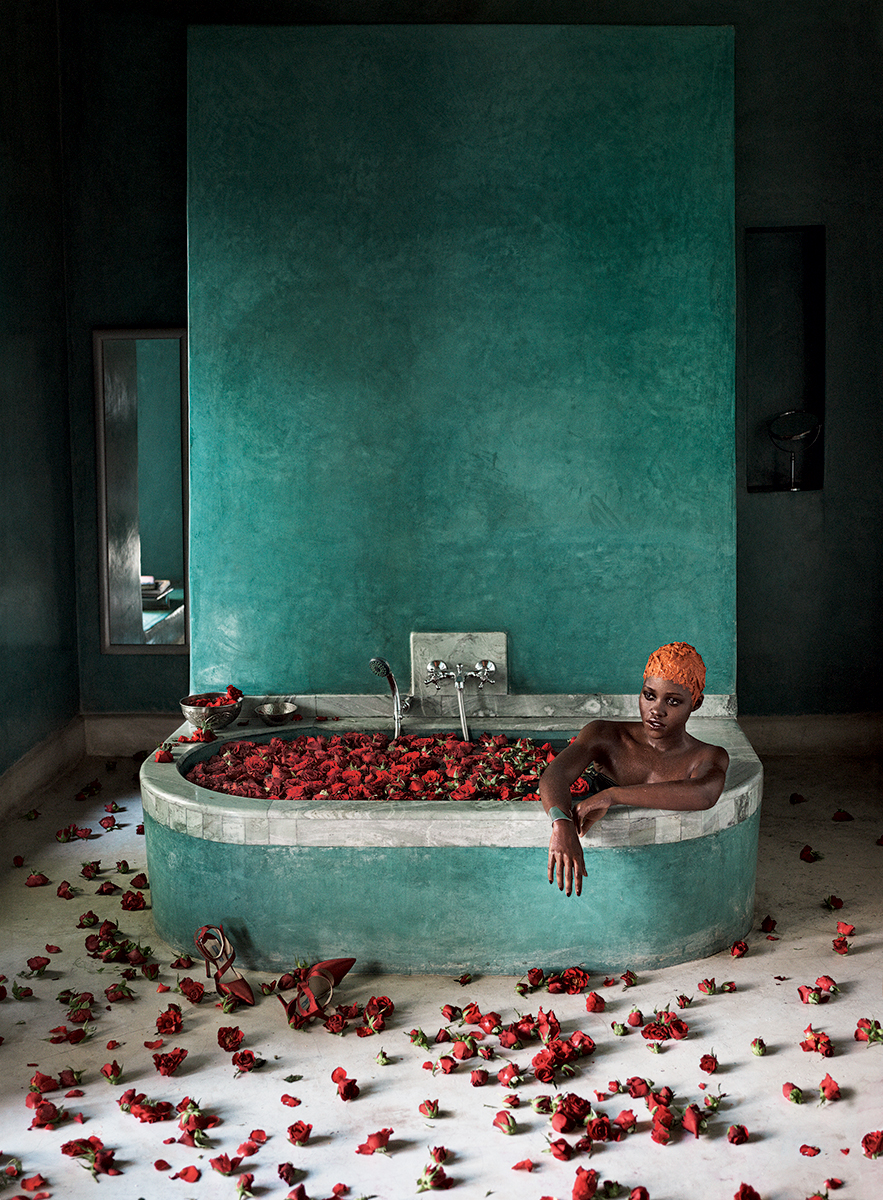 "WATER WORLD: ""It just feels like the entertainment industry exploded into my life,"" Nyong'o says, here soaking in a rose-filled bathtub at the hotel El Fenn. Janis by Janis Savitt silver cuff. Prada red satin heels. 