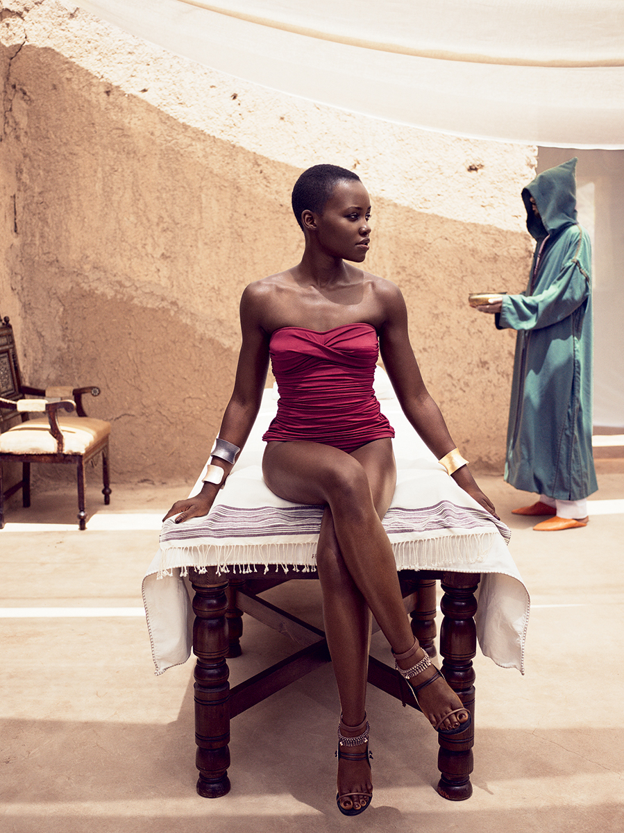 LADY IN RED: Lupita Nyong'o wearing a J.Crew swimsuit, Yossi Harari cuffs, and Casadei for Prabal Gurung heels. On set in Marrakech. | CREDIT: Vogue.com