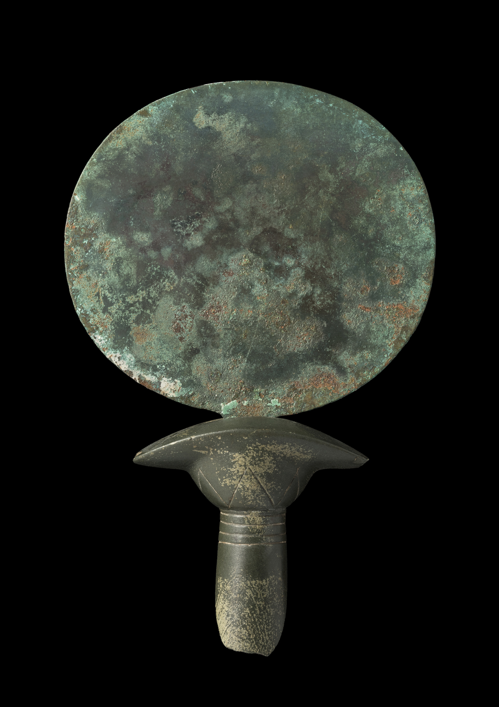 A copper alloy mirror with the upper part of a stone handle preserved in the shape of a papyrus column; Late Middle Kingdom (2055-1650 BC). Courtesy Two Temple Place and Macclesfield Museum