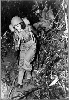 """Two United States Army nurses carry heavy combat packs on a eight-mile hike through the jungle as part of their training before taking up front-line war assignments. Before reporting for duty the American nurses learn how to combat jungle hazards and how to care both for themselves and their patients under all conditions."""