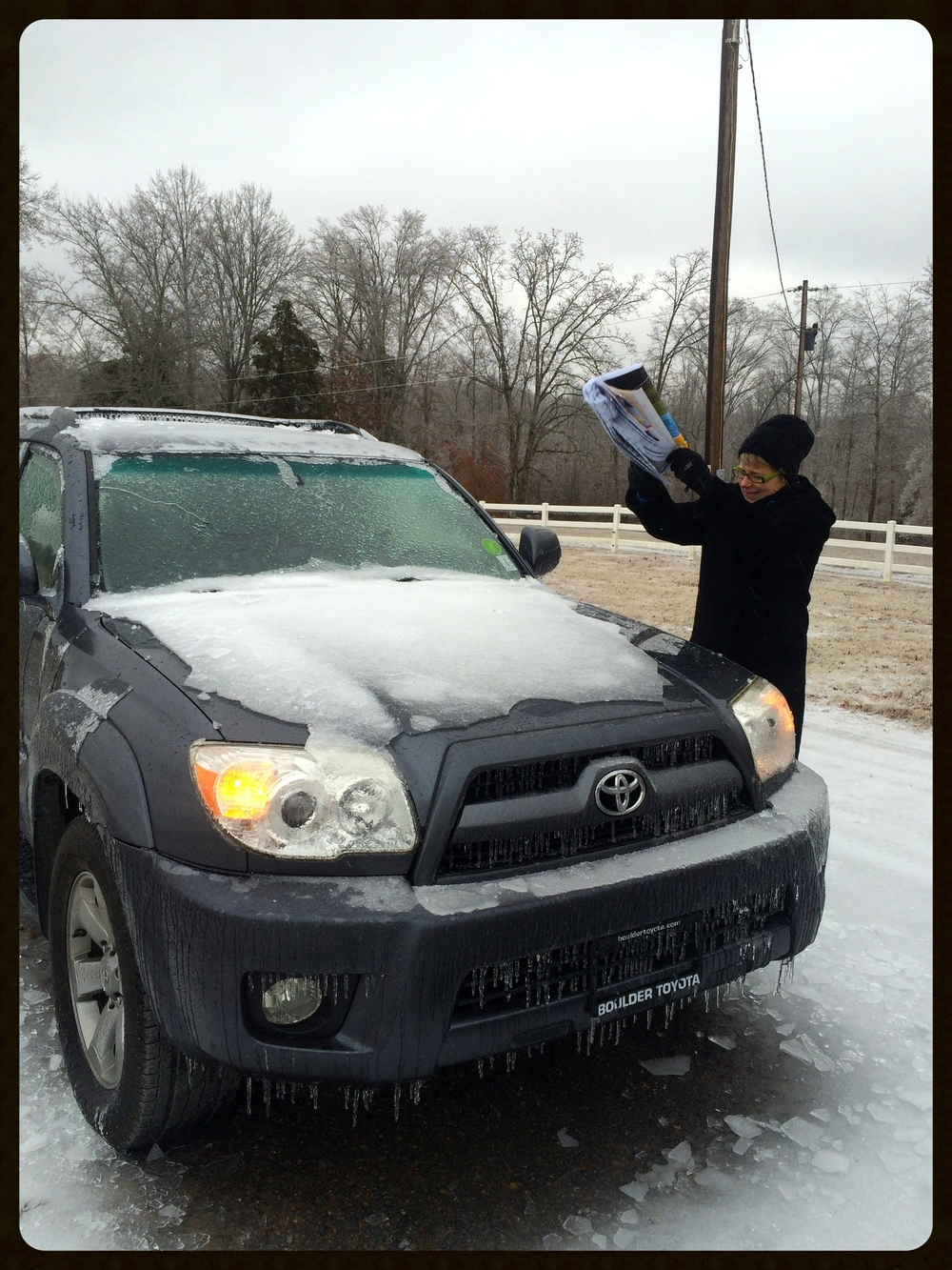My mom using a road atlas as a de-icer