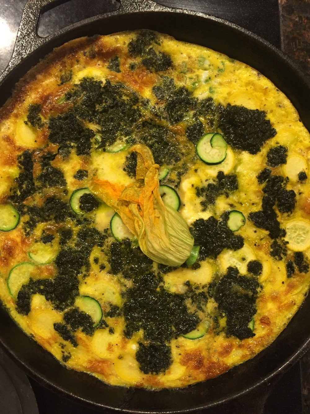 Squash, zucchini, homemade cheese, garlic scape frittata with pesto and a squash blossom on top.