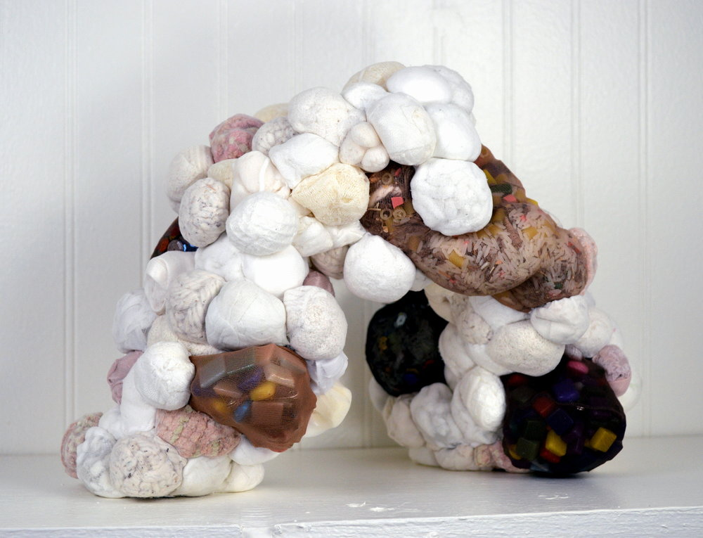 "Color Conferred  (2017) rice, glitter, sequins, rhinestones, nylon stockings, towels, q-tips, rug mats, mop, sponges, silk slips, bath loofahs, napkins, bath mats, balloons, packing peanuts, cotton balls, face pads, underwear, diaper pins, pasta, mosaic tiles, waxed linen thread 14"" x 18"" x 12"" * Title inspired by the poem ""C-Section"" by Alexis Pauline Gumbs"