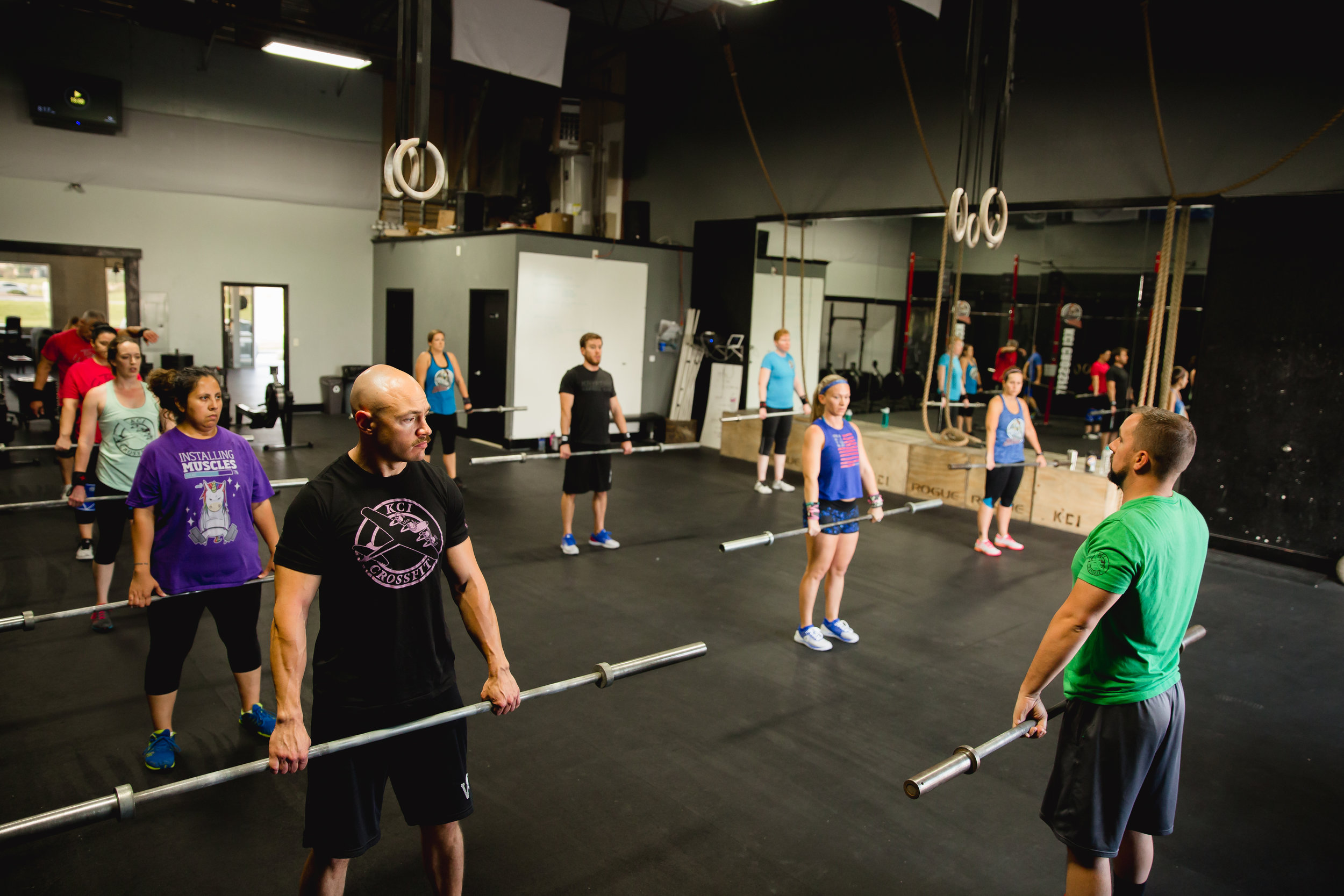 CrossFit gym coach in Kansas City teaching safe barbell movement.