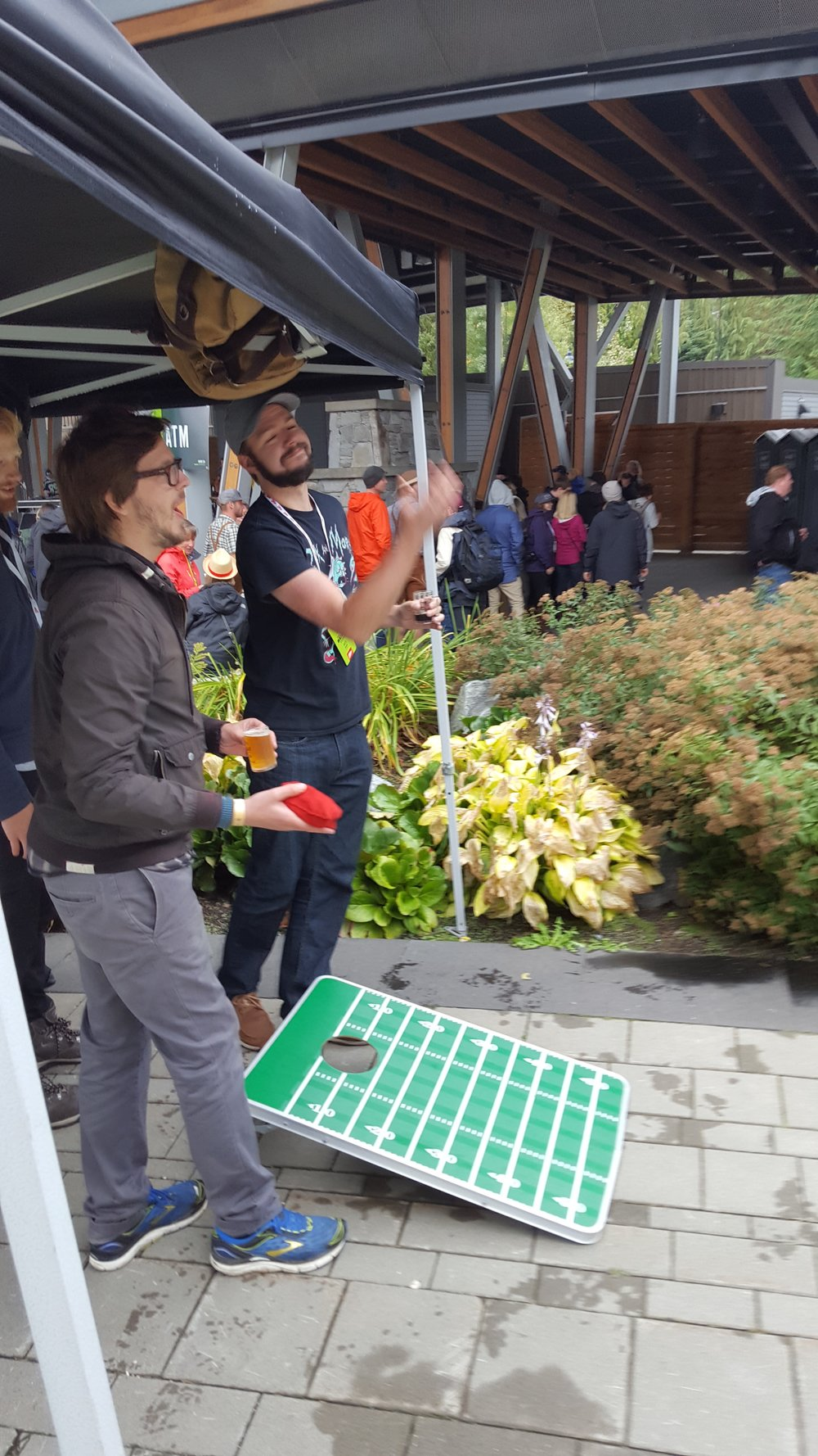 Mike Doan takes some time away from pouring samples to play some Cornhole with the On Tap Crew