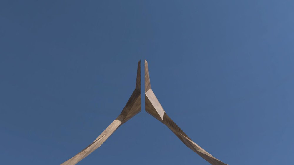 Looking upward, the viewer sees a sliver of the sky separating the halves.