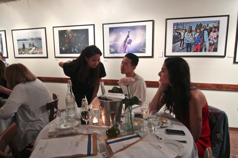 "Dinner guests at ""SUSPEND REVISITED"" with photography displayed by Kayla Reefer and Diane Abapo in the background (Aug 20). / Photo: © Christy J. Kim"