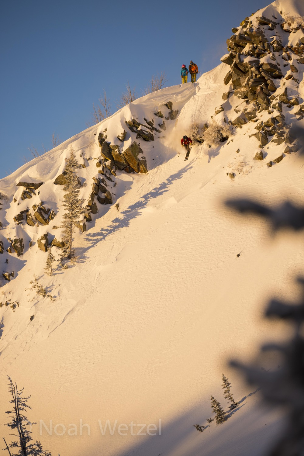 Wille Nelson and Lucy Sackbauer watch as Chris Brule drops into the first line of the morning. Brighton Resort, Utah