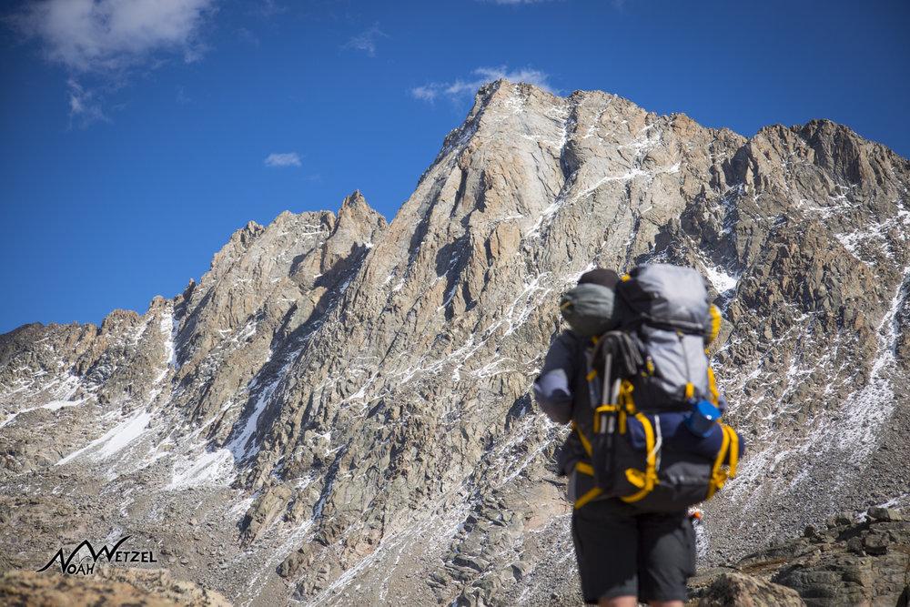 Ben Wetzel dwarfed by Harrower Peak. Indian Basin. Wind River Range. Wyoming