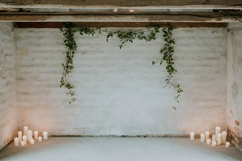 rustic wedding ceremony decor with green foliage and lots of candles