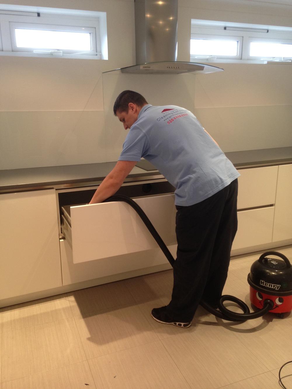 cleaner hoovering cupboards.jpg