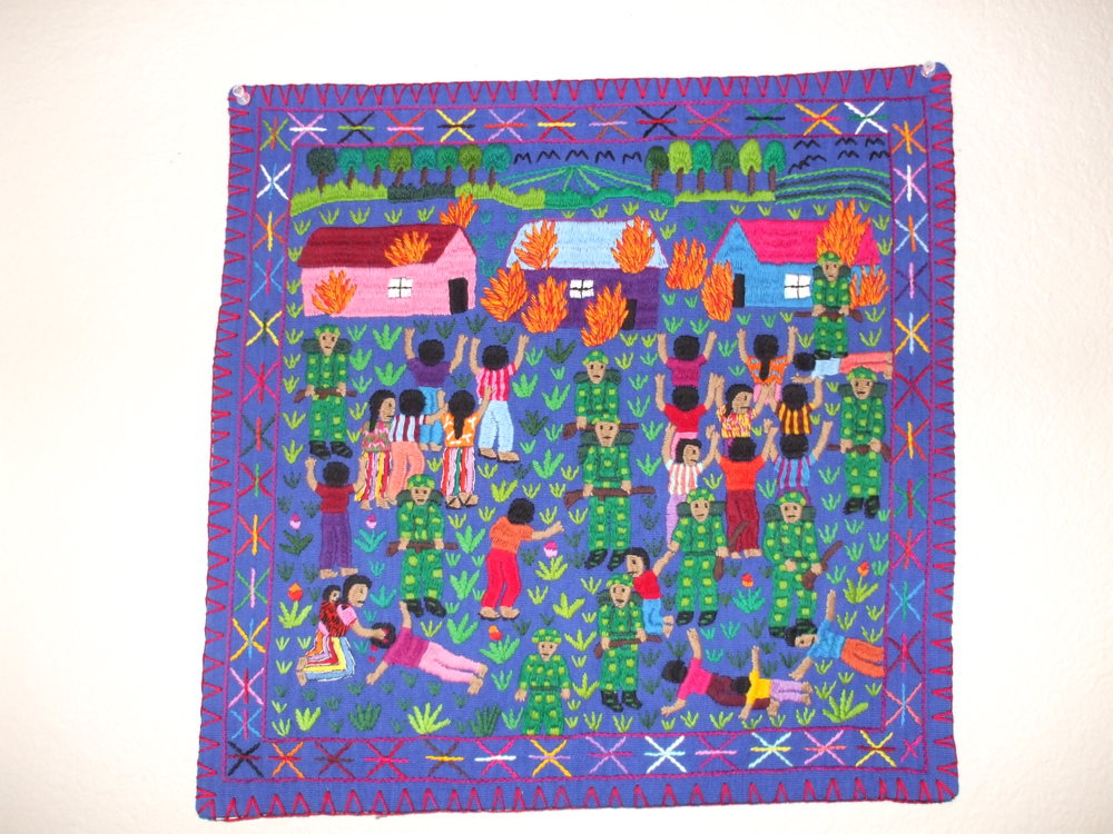 This arpillera is from a workshop in Guatemala started by Ramelle Gonzalez. She had to teach the Mayan women to embroider since they previously used weaving. Polyester yarn on cotton background. Photo courtesy of Dr. Deborah Deacon.