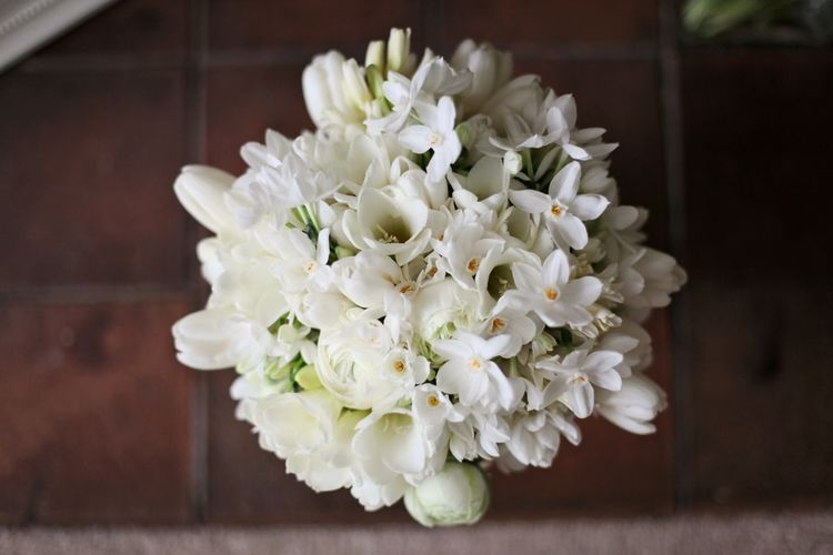 All white spring wedding bouquet with ranuncula, freesia, and narcissi., Dorton House, Bucks.