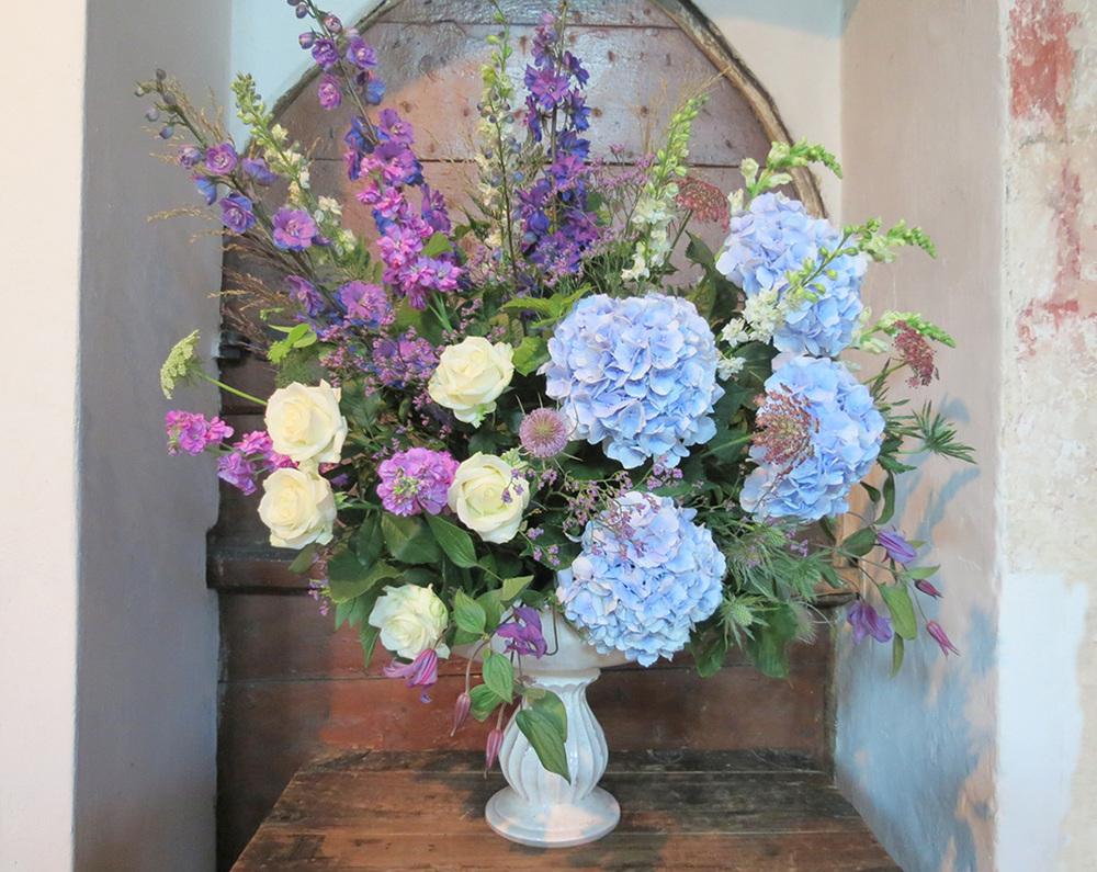Wedding display with tall purple delphinium and blue hydrangea, Padbury Church, Bucks