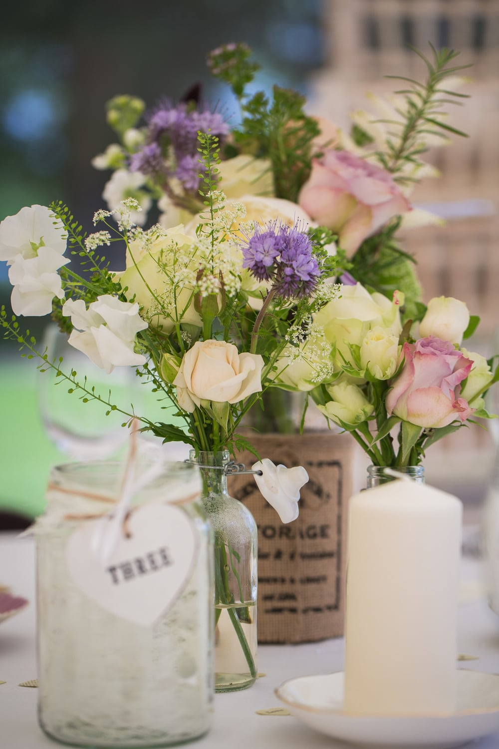 Rustic jam jar of flowers on wedding table