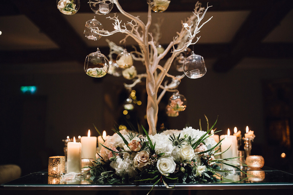 Christmas wedding centrepiece with manzanita tree, floral base & glass baubles at Notley Abbey Bucks