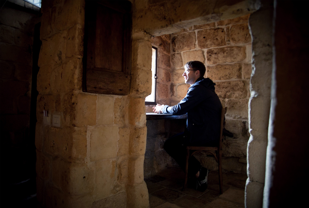 My husband David sitting at the little letter writing desk in our room at the Sextantio Le Grotte della Civita in Matera, Italy, 2013.