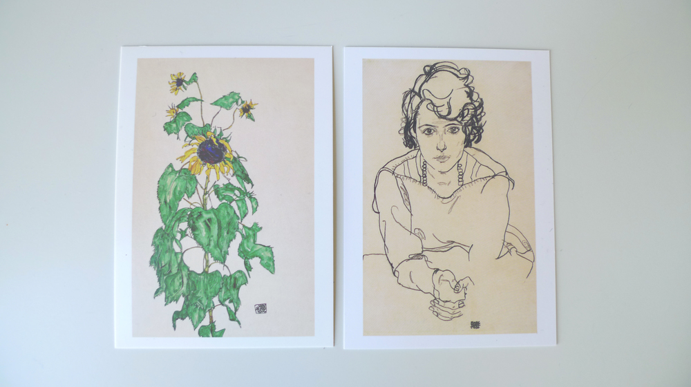 Two Egon Schiele postcards from the Neue Galerie shop: Sunflower, 1916 (left) and Seated Woman, 1918 (right)