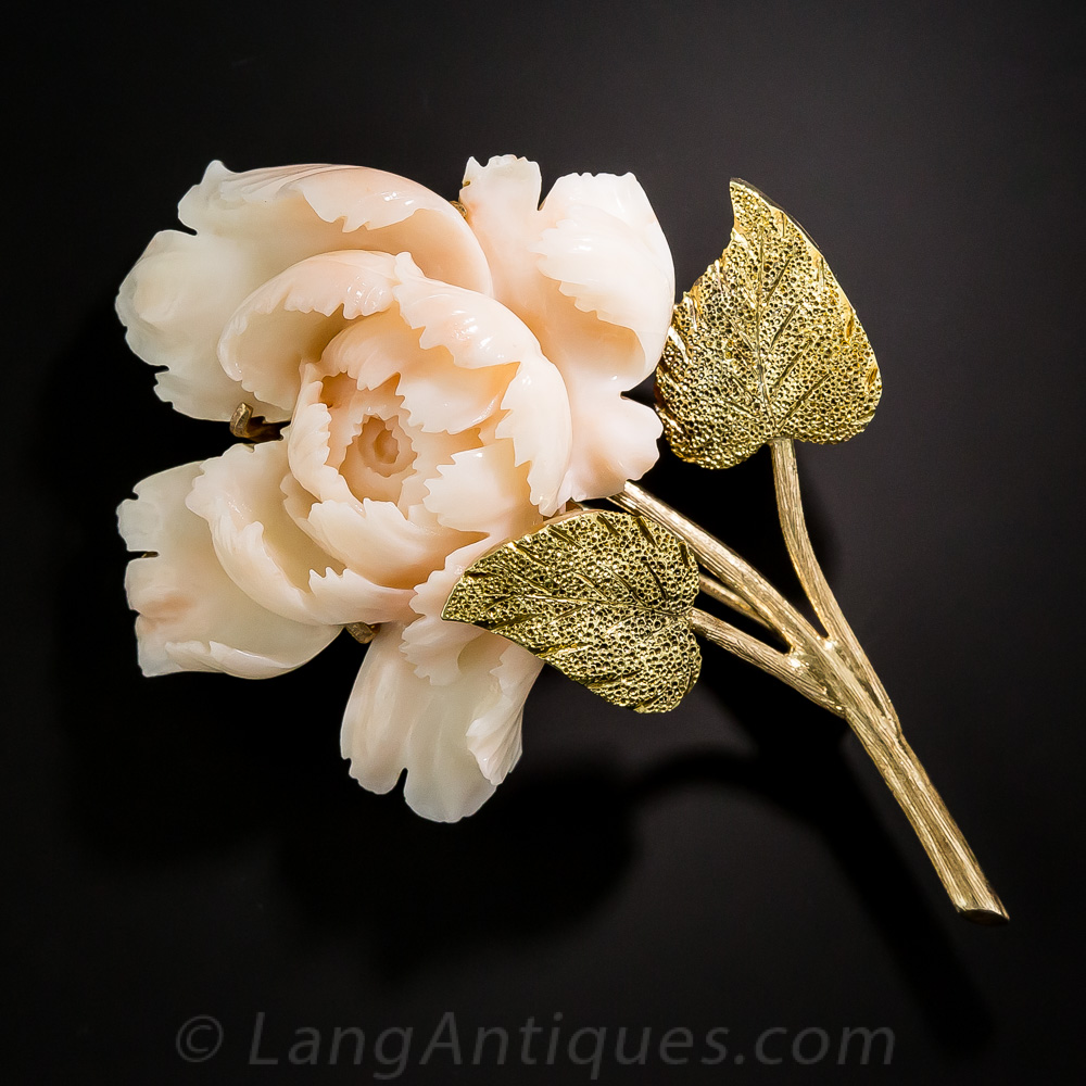 Long regarded as an omen of good fortune and happy marriage, this precious peony brooch, circa 1940s-50s, is lovingly rendered in hand carved angel skin coral with realistically textured 14K gold stem and leaves that beautifully support the deckle-edged, wispy folds of the lush, full bloom. From Lang Antiques