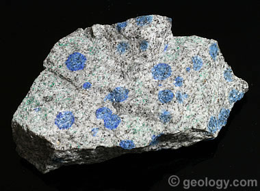 A piece of dry K2 Granite. A wet surface would increase the intensity of the blue azurite orbs. This piece is approximately 10 centimeters across, and the largest azurite orbs are about 1 centimeter across.