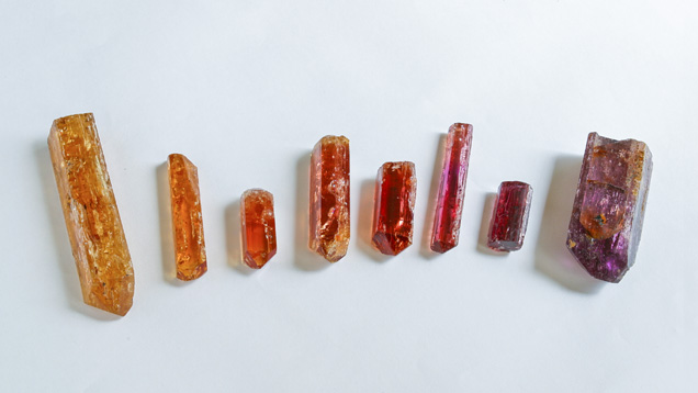 TOPAZ CRYSTALS ARE TYPICALLY ELONGATED, WITH GROOVES PARALLEL TO THEIR LENGTHS. FOR THIS REASON, THEY'RE COMMONLY CUT INTO LONG OVAL OR PEAR SHAPES. THESE CRYSTALS SHOW ORANGE, PINK, AND BROWN COLORS. - ERIC WELCH/GIA