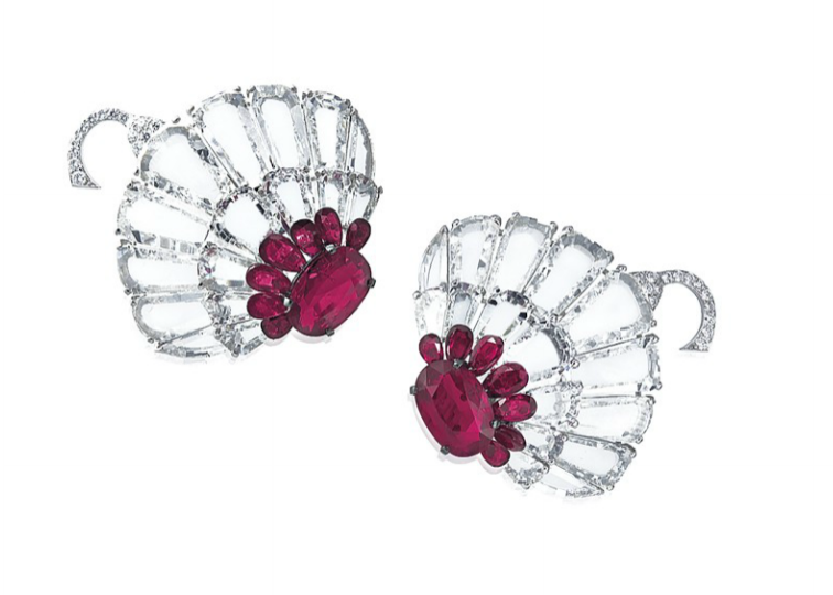 A pair of ruby and diamond earrings by Bhagat. Stylised lotus flowers with central rubies surrounded by flat diamond petals.