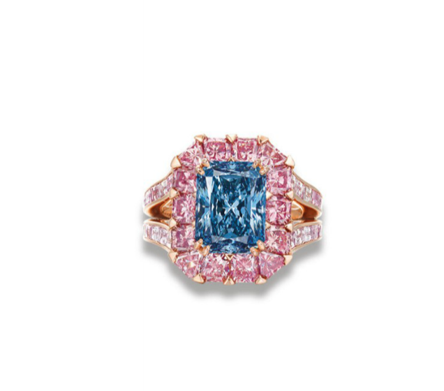 An exceptional colored diamond ring by Moussaiff. The rectangular-cut fancy vivid blue diamond, weighing approximately 3.98 carats, within a cushion and triangular-shaped pink diamond surround.