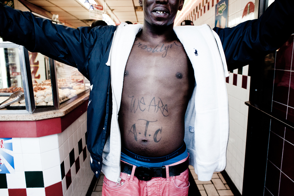 A young man shows off his Addicted To Cash tattoo, 2013.