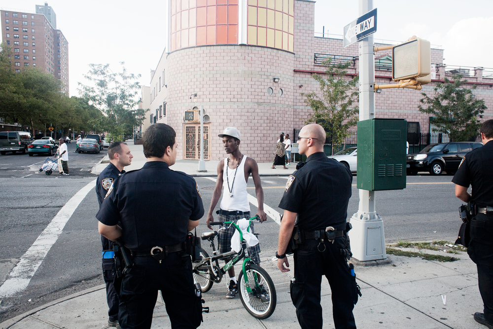 Police stop and question a young man on a bike, 2012.