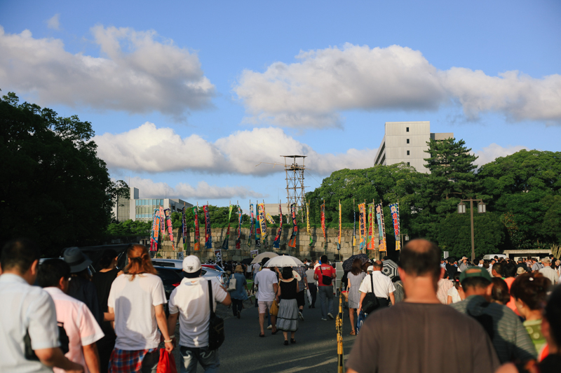 Making our way out of the stadium. Nagoya castle is right next to the stadium and a watch tower over looks over a moat, containing two men playing the drums as everyone exited the premises.