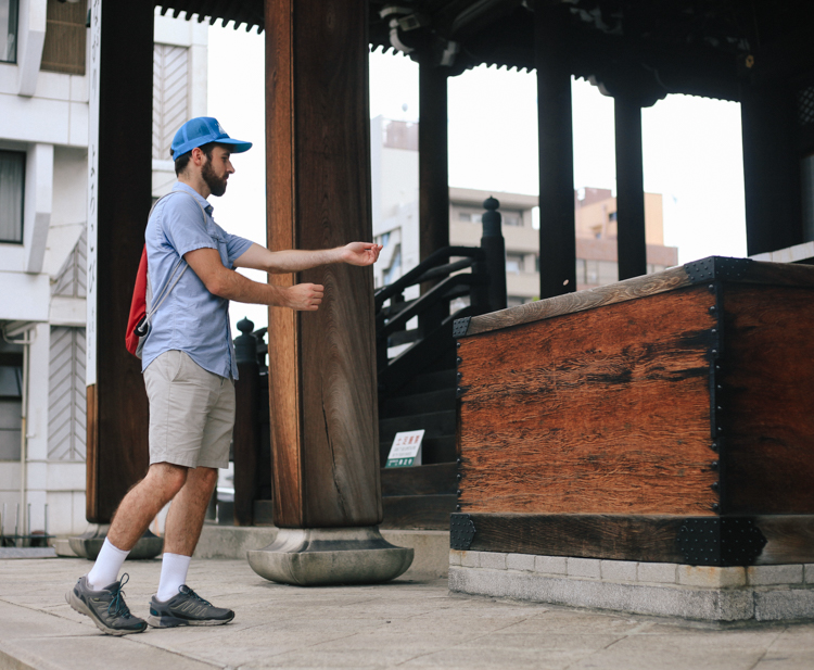 Zac throwing some change into a wooden box right outside one of Kyoto's oldest temples.
