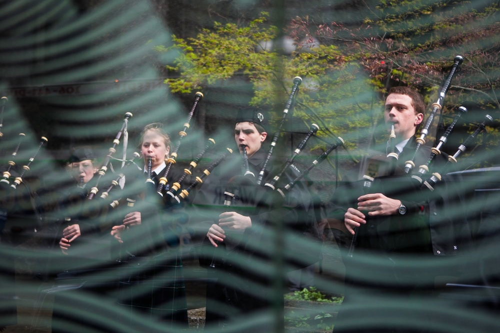 Seen through a bus stop, members of The Northwest Junior Pipe Band practice before the annual St Patrick's Day Parade in this photo from Saturday, March 14, 2015. Hundreds gathered in downtown Seattle to celebrate Irish culture and traditions with marching bands, performers and more.