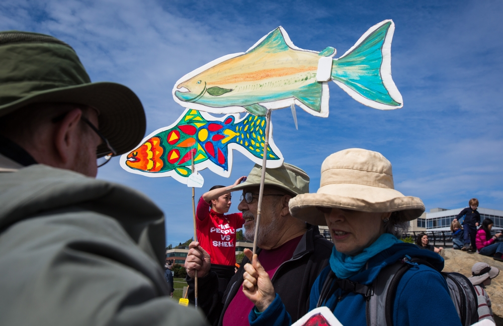 "Protesters hold up paper fish during a protest against the planned arrival of Shell's oil drilling rig at Myrtle Edwards Park on Sunday, April 26, 2015. Hundreds gathered for the ""Shell No: Seattle Draws the Line"" protest organized by various organizations to combat increased climate change and possible damage to the Arctic."