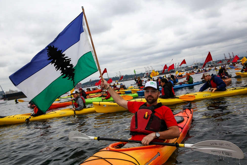 A man holds up a Cascadian flag as hundreds of kayaktivists take to the water during protest against drilling in the Arctic and the Port of Seattle being used as a port for the Shell Oil drilling rig Polar Pioneer. The protest flotilla drew many paddlers to show their displeasure with the rig being moored in Seattle. Photographed on Saturday, May 16, 2015.