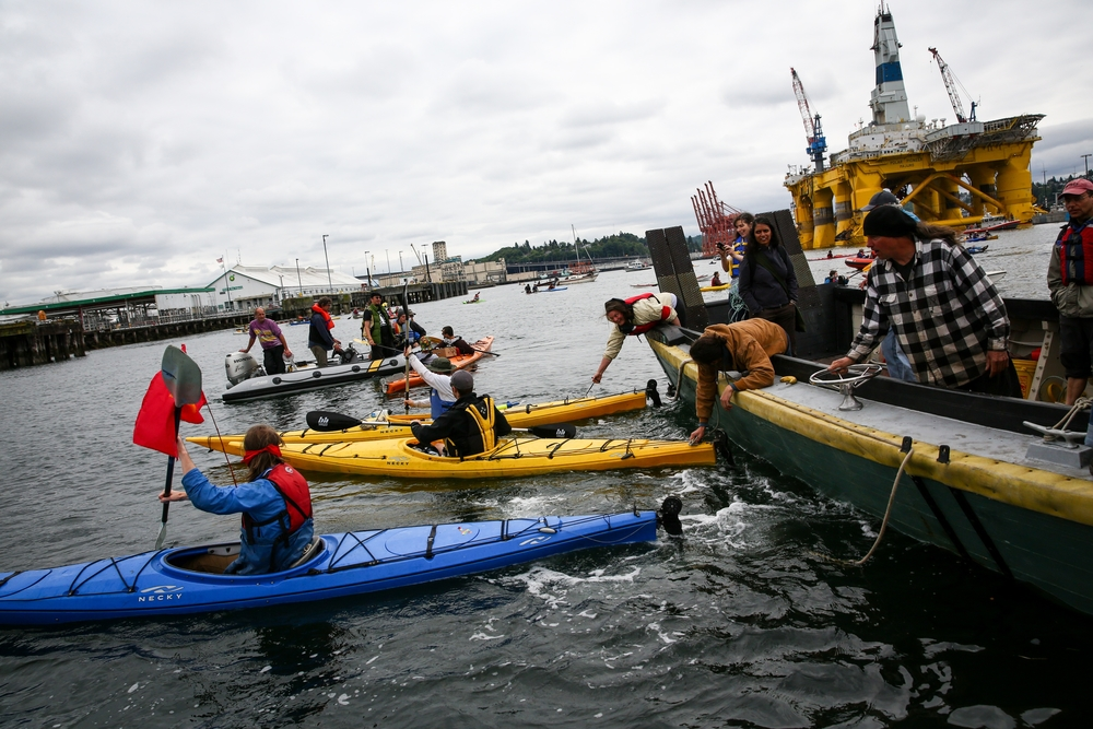 People use kayaks to position a protest boat as hundreds of kayaktivists take to the water during protest against drilling in the Arctic and the Port of Seattle being used as a port for the Shell Oil drilling rig Polar Pioneer. The protest flotilla drew many paddlers to show their displeasure with the rig being moored in Seattle. Photographed on Saturday, May 16, 2015.