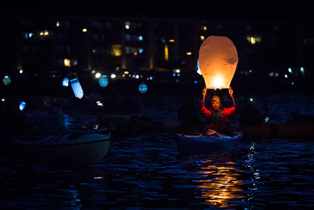 A kayaktivists prepares to release a lantern during a luminary flotilla protesting Shell's oil rig and proposed arctic drilling.