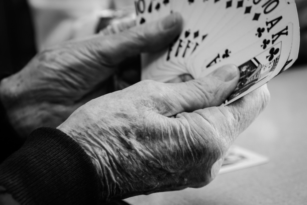 "Ralph Carmichael, 90, cradles his cards in a game of Pinochle at the senior center. Carmichael keeps a USB drive in his pocket that contains his entire ""history"" as he calls it."