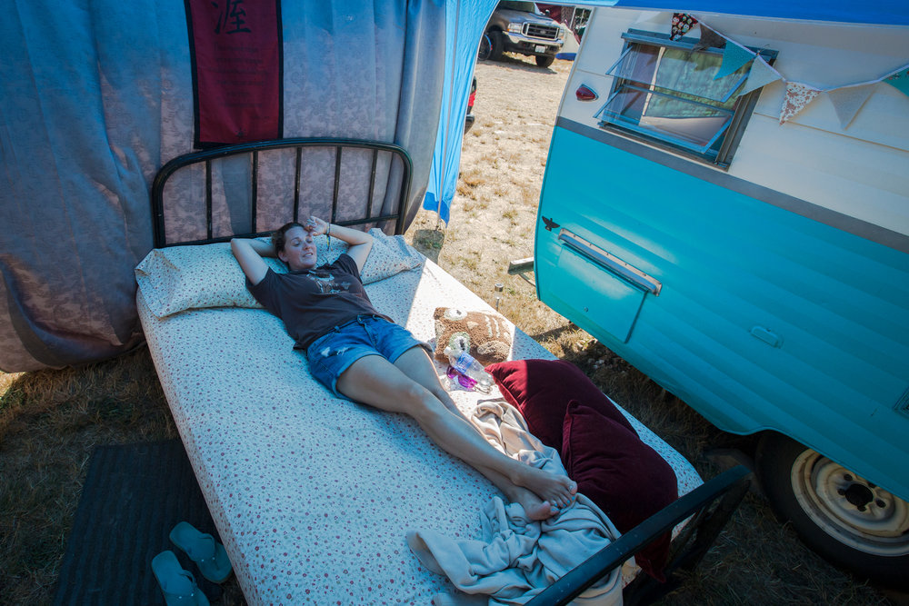 Jen Grube stretches out on her bed after setting up her campsite as day one of Summer Meltdown kicks off on Thursday, Aug. 11, 2016 in Darrington, Wa.