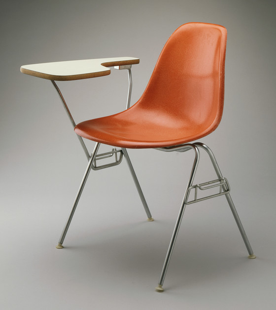 DSS Plastic Stacking Chair with Table Arm by Charles and Ray Eames, 1960–61.© Eames Office LLC