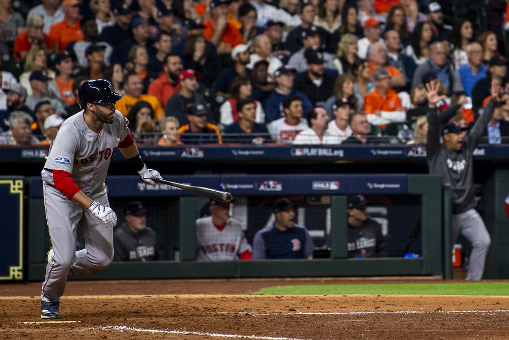 October 17, 2018, Houston, TX: Boston Red Sox outfielder J.D. Martinez puts the ball in play as Boston Red Sox Manager Alex Cora celebrates in the background as the Boston Red Sox face the Houston Astros in Game 4 of the ALCS at Minute Maid Park in Houston, Texas on Wednesday, October 17, 2018. (Photo by Matthew Thomas/Boston Red Sox)