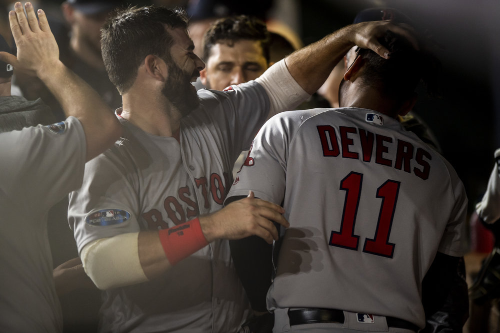 October 18, 2018, Houston, TX: Boston Red Sox first basemen Mitch Moreland hugs,  Boston Red Sox third basemen Rafael Devers in the dugout after Devers hit a home run as the Boston Red Sox face the Houston Astros in Game 5 of the ALCS at Minute Maid Park in Houston, Texas on Thursday, October 18, 2018. (Photo by Matthew Thomas/Boston Red Sox)