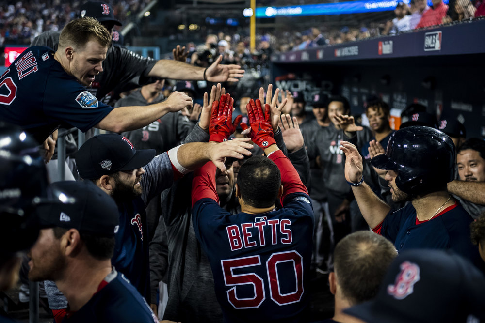 October 28, 2018, Los Angeles, Ca: Boston Red Sox outfielder Mookie Betts is greeted with high-fives in the dugout after hitting a home run as the Boston Red Sox face the Los Angeles Dodgers in Game 5 of the World Series at Dodger Stadium in Los Angeles, California on Saturday, October 28, 2018. (Photo by Matthew Thomas/Boston Red Sox)