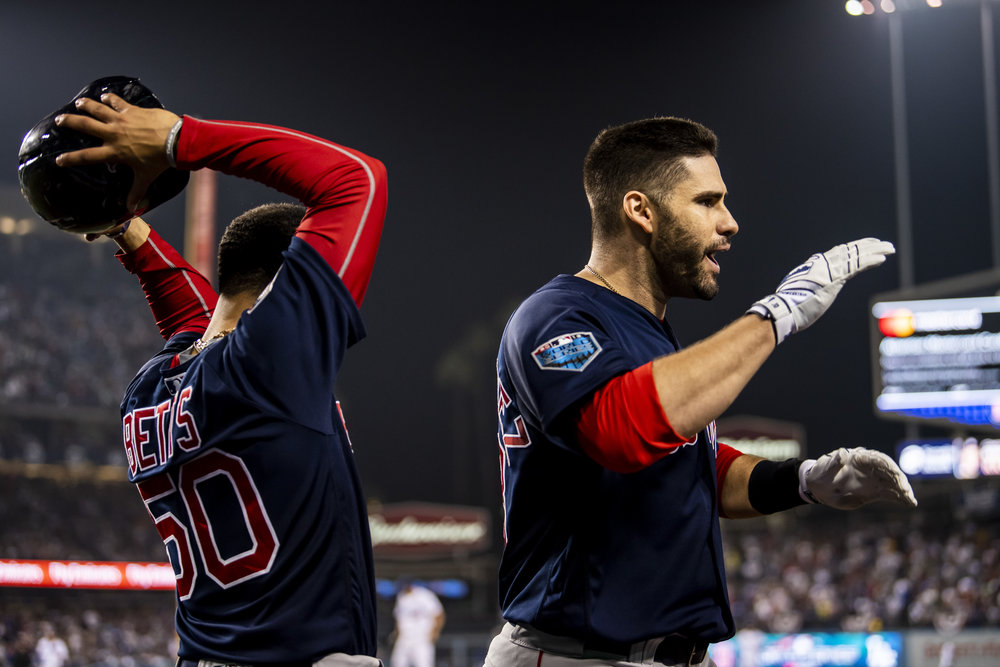 October 28, 2018, Los Angeles, Ca: Boston Red Sox outfielder Mookie Betts lifts off Boston Red Sox outfielder J.D. Martinez's helmet after a home run as the Boston Red Sox face the Los Angeles Dodgers in Game 5 of the World Series at Dodger Stadium in Los Angeles, California on Saturday, October 28, 2018. (Photo by Matthew Thomas/Boston Red Sox)